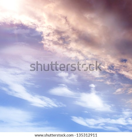 A sky with dark clouds and sun - stock photo