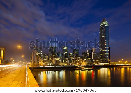 A skyscraper and modern buildings in the St George Wharf quarter in Vauxhall, London at night with the Vauxhall Bridge in the foreground - stock photo
