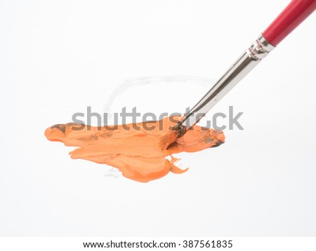 A slanted paint brush with orange paint over a white paper with stain - stock photo