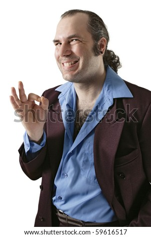A sleazy car salesman, Con man, or pimp, wearing a retro suit and smiling with a large cheesy grin. - stock photo