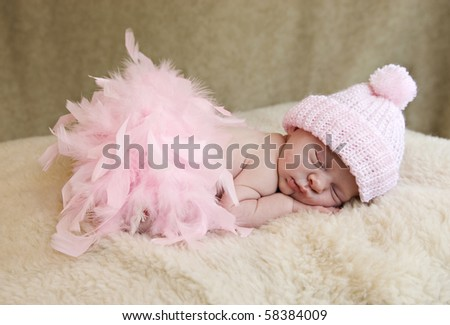 A sleeping baby girl wearing pink hat and pink feather boa, soft focus - stock photo