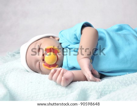 A sleeping baby with a silicone pacifier