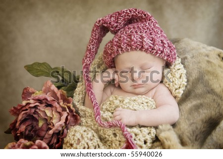 A sleeping newborn baby girl in crocheted  cocoon wearing hat with vintage looking setup, selective focus with focus on face