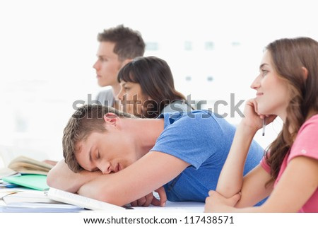 A sleeping student in class as the other students pay attention and stay awake - stock photo