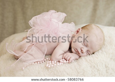A sleeping three week old baby girl with pink bow and pearls, soft focus - stock photo