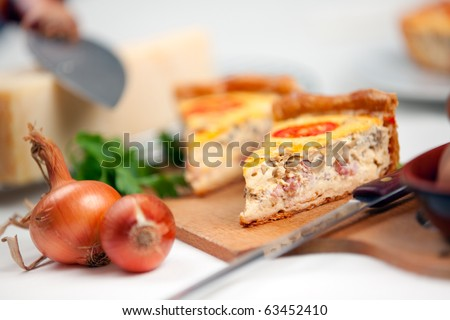 A slice french quiche lorraine with bacon , mushrooms and cheese. Shallow depth of field on quiche slice