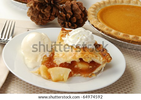 A slice of apple pie by a sweet potato pie and pine cones - stock photo