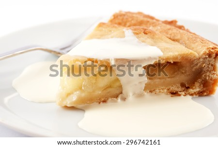 A slice of apple pie on a plate with cream on top - stock photo