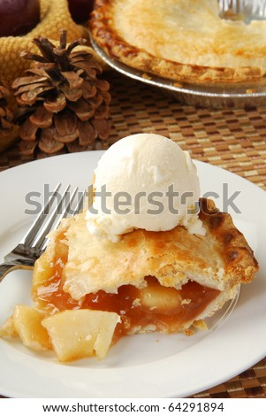 A slice of apple pie with french vanilla ice cream in a beautiful autumn table display - stock photo