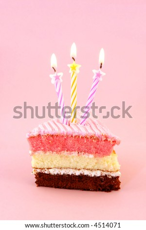 A slice of birthday cake with starry birthday candles. - stock photo