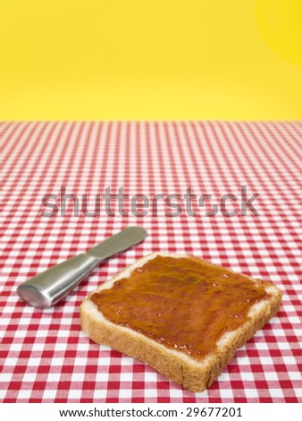 A slice of bread spread with jam and a knife over the table.