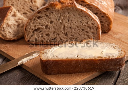 A slice of bread with butter on a chopping board. - stock photo