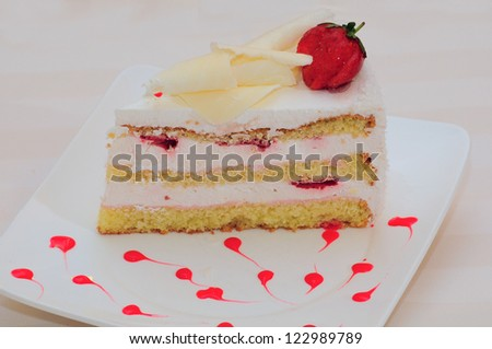A slice of cake topped with white chocolate and strawberry
