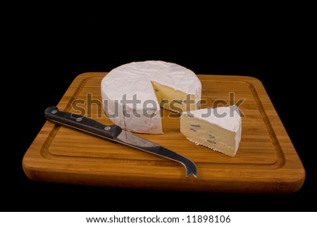 A slice of Cambozola cheese on a wooden board with a knife for soft cheese - stock photo