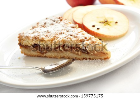 A slice of delicious apple pie with apple slices in the back  - stock photo