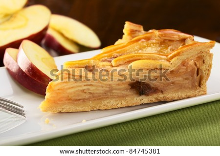 A slice of delicious apple pie with apple slices in the back (Selective Focus, Focus on the left front part) - stock photo
