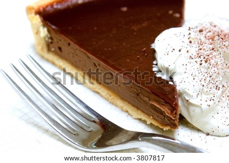 A slice of delicious chocolate tart gateaux served with fresh whipped cream with sprinkling of chocolated dust. - stock photo