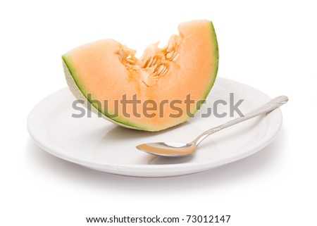 A slice of fresh, juicy cantaloupe on a white plate and white background. Seeds in.
