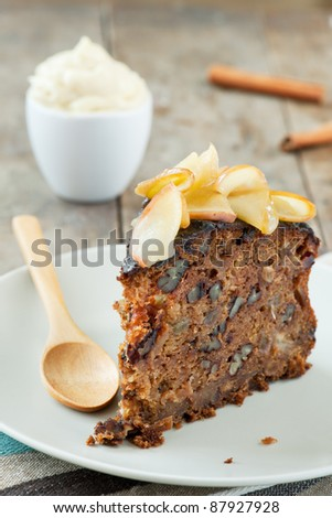 A slice of home baked apple cake with a cup of whipped cream in the background and some cinnamon sticks, on a wooden table with spoon next to it. - stock photo