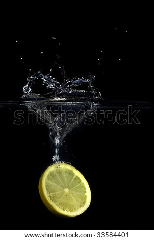 A slice of lemon dropped into water creating a heart shaped splash. Isolated on black. - stock photo