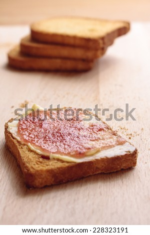 A slice of melba toast with butter and fruit jam and a few more in the background on a wooden board - stock photo