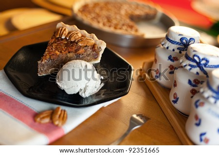 A slice of pecan pie served with vanilla ice cream on a black dish. Shallow depth of field on the pie slice.