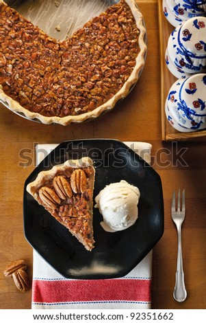 A slice of pecan pie served with vanilla ice cream on a black dish, the whole pie in the background. - stock photo