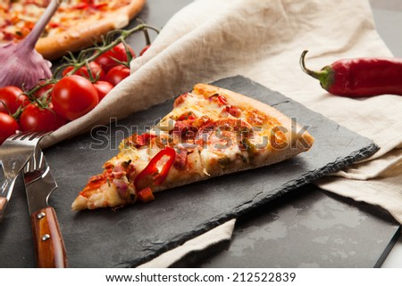 A slice of pizza is on a stone plate around her ingredients closeup - stock photo