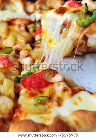 A slice of pizza with melting cheese - stock photo