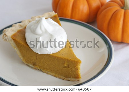 A slice of pumpkin pie garnished with whipped cream.