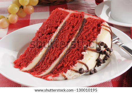 A slice of red velvet cake with chocolate chip icing - stock photo