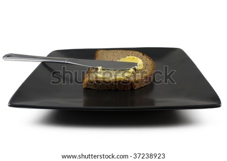 A slice of rye health bread with butter spread - stock photo