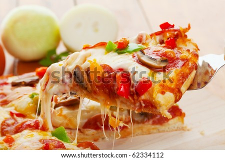 A Slice of supreme pizza being lifted up - stock photo