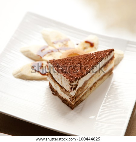 A slice of the Italian delicacy tiramisu and several piece of banana on dish - stock photo