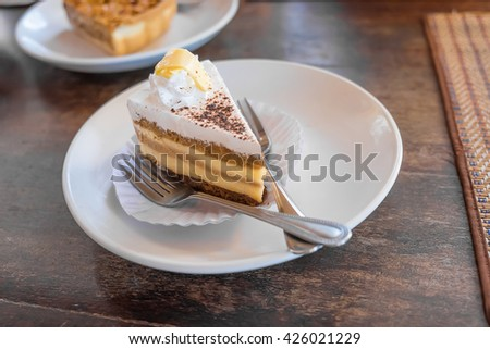 A slice of tiramisu cake on a plate and ready to eat, in coffee shop, Shallow DOF - stock photo