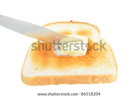 A slice of toast being buttered with a knife, isolated on white.