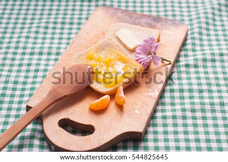 A slice of toast with honey, a slice of bread with butter, two slices of orange, a flower, a wooden spoon on the wooden desk