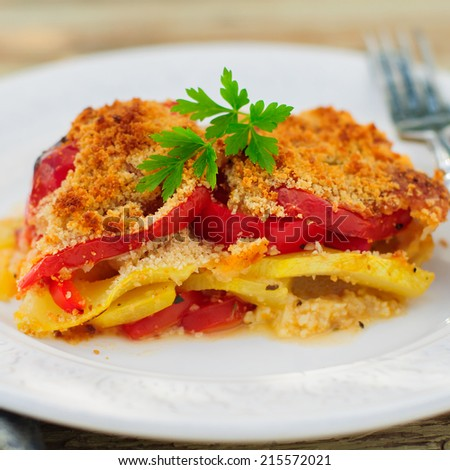 A Slice of Tomato, Red Capsicum, Zucchini and Feta Gratin with Dry Bread Crumb Crust, close up, square - stock photo