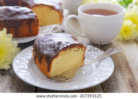 A slice of vanilla cake and a cup of cake - stock photo