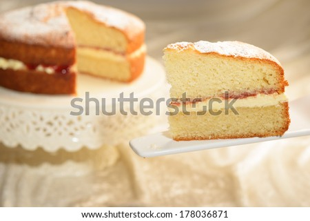 A slice of Victoria sponge cake with cut cake in the background - stock photo