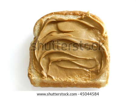 a slice of white bread with creamy peanut butter spread on it against white. - stock photo