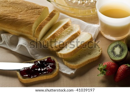 a sliced bread with jam, fruit and fruit juice on a table. - stock photo