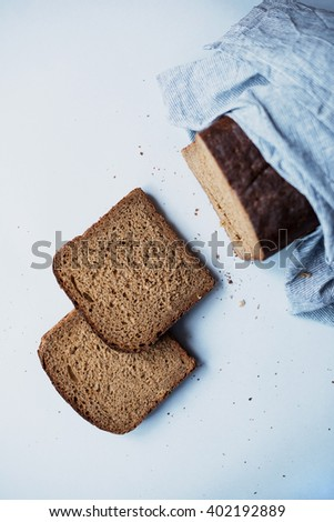 A sliced loaf of black bread wrapped in kitchen towel from top on light grey background - stock photo