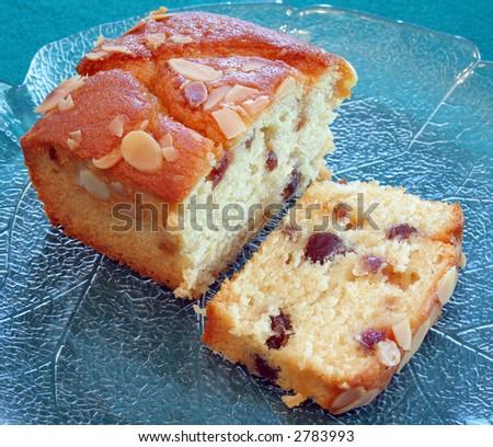 A sliced moist fruit cake on a glass platter - stock photo