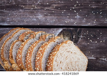 A sliced  whole grain bread with sesame seeds. Sliced bread for sandwiches on a wooden table.   - stock photo