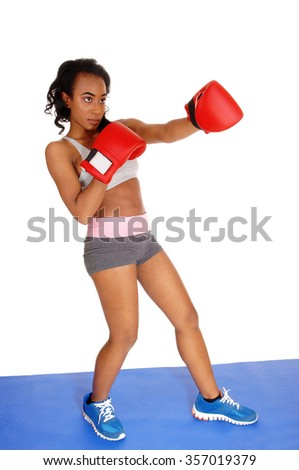 A slim African American girl standing on a blue mat during boxing exercisewith red gloves, isolated for white background. - stock photo