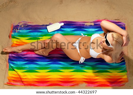 A slim blond woman in a white bikini lying on a colourful beach towel sunbathing