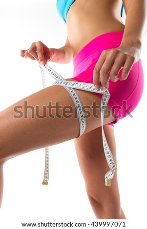 A slim girl measuring her waist, close-up. - stock photo