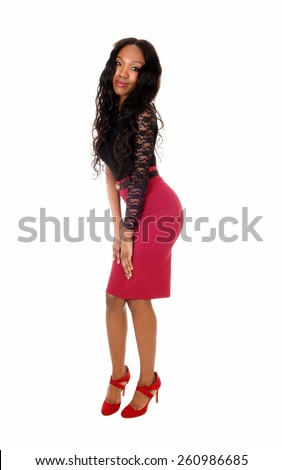 A slim tall African American woman standing in a red skirt and long curly
