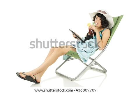 A slim young teen chilling out on a beach chair in her beach outfit with her tablet computer and iced tea.  On a white background.